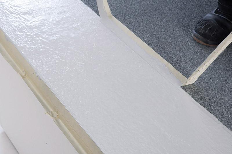 Verschlichten des Materials und Entfernen des Klebebandes in frischem Zustand. Das Ergebnis ist ein regelkonform und sauber abgedichtetes Traufblech.